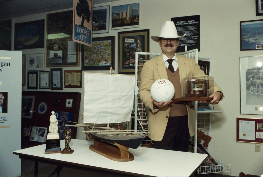 Mayor Mike Harcourt posing in a cowboy hat in front of a display of some of Vancouver's Centennial gifts. Reference code AM1576-S6-12-F49-: 2011-010.2027