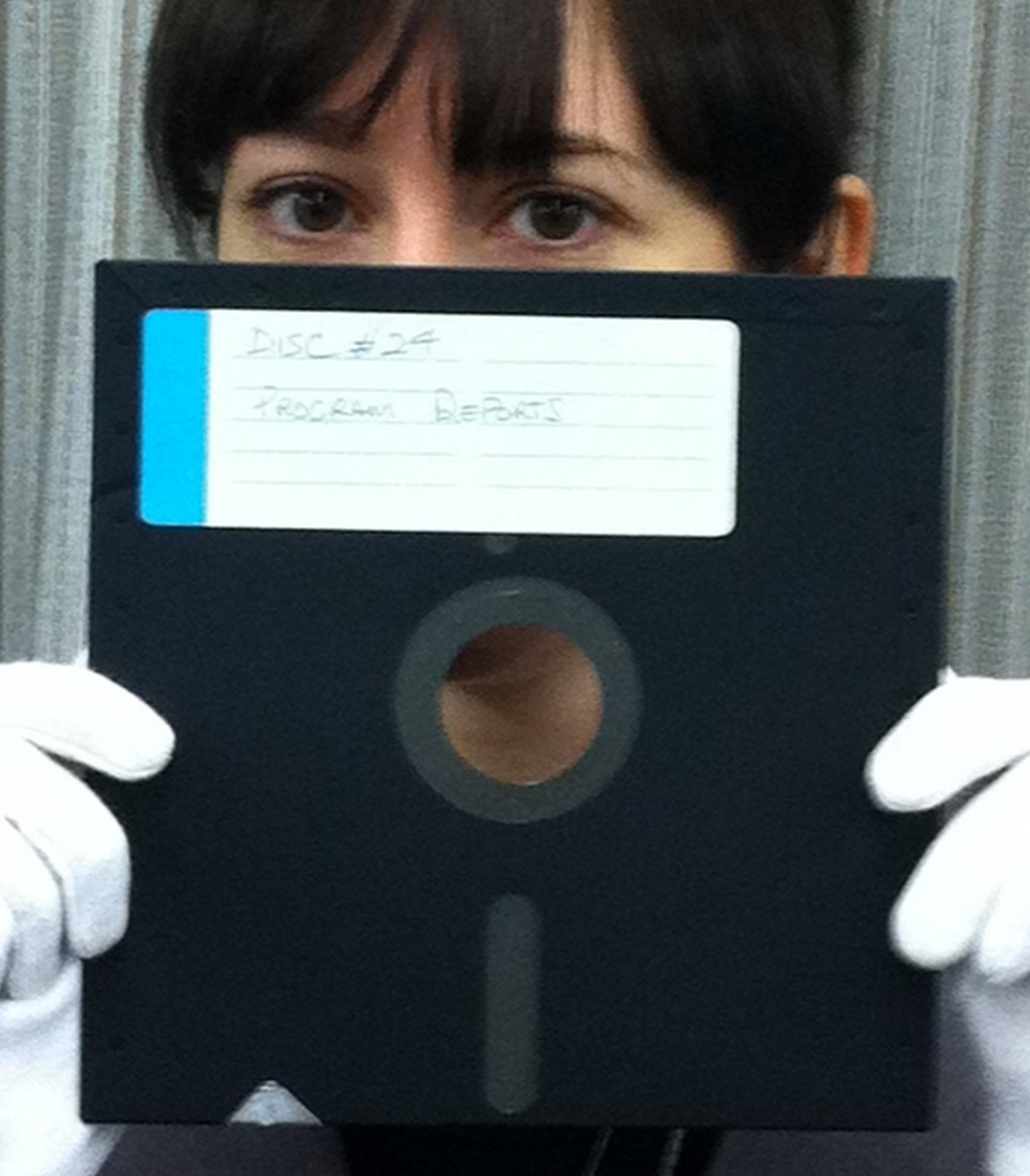 Archivist holding an 8-inch floppy disk