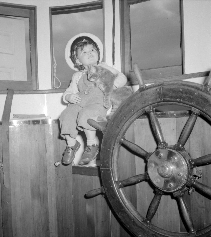 Girl holding cat in wheelhouse, 1942 Jack Lindsay, Photographer. Reference code AM1184-S3-: CVA 1184-1488