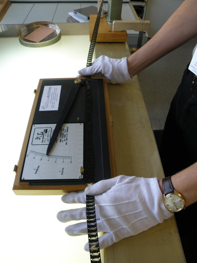 An archives volunteer uses a shrinkage gauge to measure how much the film has shrunk over time. Film that has shrunk significantly must be handled with extra care when being digitized.