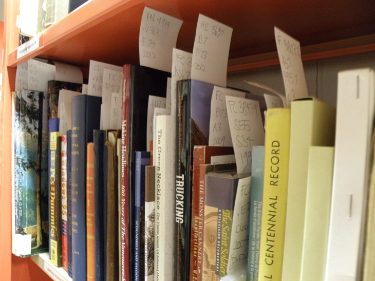 Books on the shelf with Library of Congress bookmarks ready for labeling. Photo by Allison Hasselfield.]