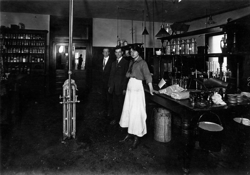 Pictured here are three of the BC Sugar laboratory staff members in 1916: Maggie McKenzie, Ernie Abbott, and R.B. This photograph was taken on second floor office building at BC sugar. Reference code: 2011-092.1854.