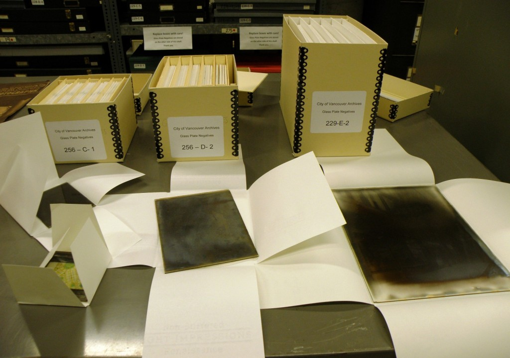 Three standard box sizes and some examples of glass negatives with their four-flap enclosures open.
