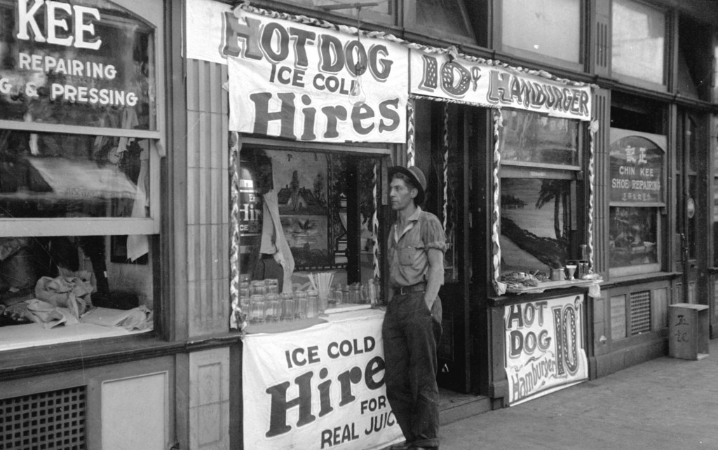 Man standing outside shallow building at Pender and Carrall Streets, 1936. Reference code: AM54-S4-: Bu N158.3