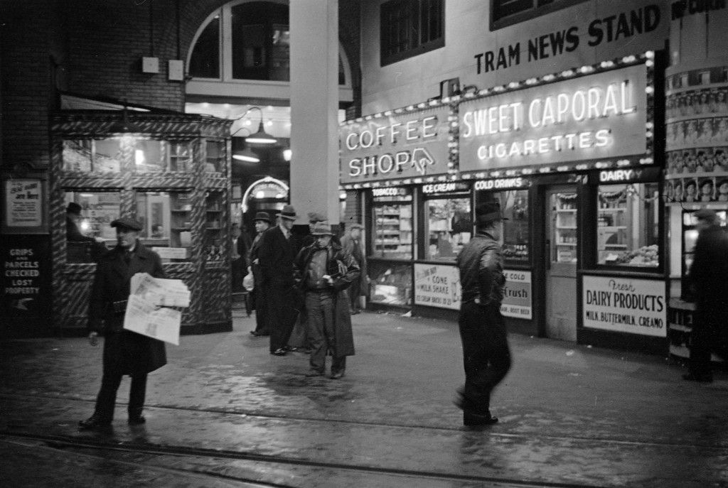 The Tram News Stand and Coffee Shop illuminated at night in the B.C. Electric Building at 425 Carrall Street, 1937. James Crookall, photographer. Reference code: AM640-: CVA 260-778