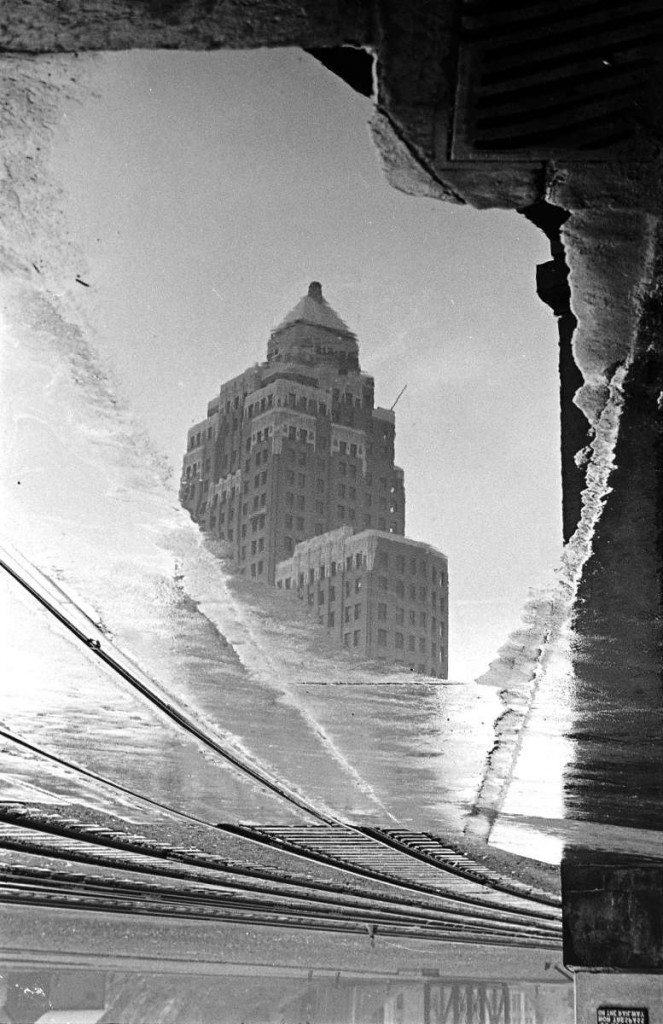 Train tracks and a reflection of the Marine Building in the water (c. 1939). Reference code: AM640-S1-: CVA 260-999.