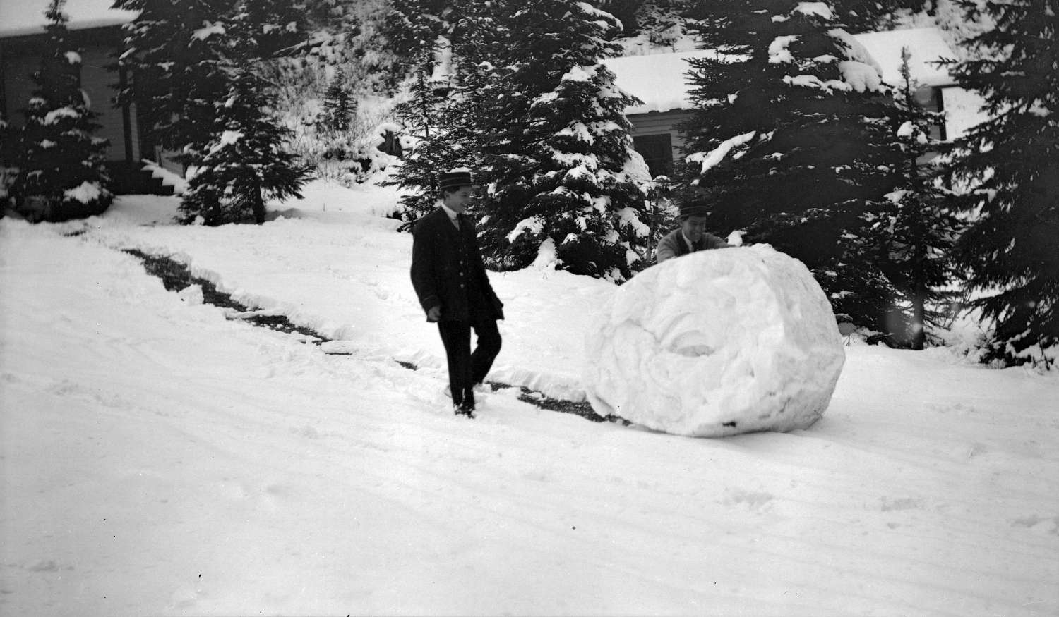 Two men rolling a snowball