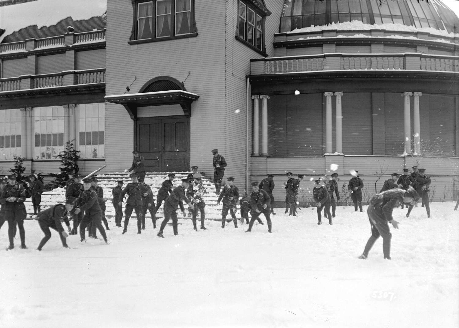 Men in uniform throwing snowballs