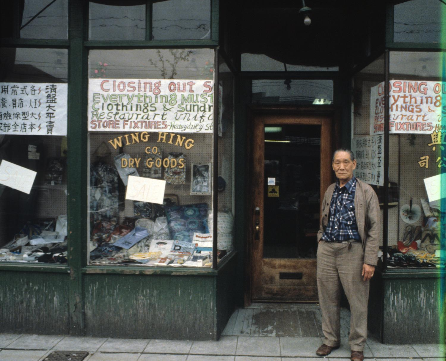 Wing Hing Dry Goods owner Lin Bei-lian standing at the front entrance to his shop prior to the business's final closure. In the 1970s and 1980s, Yee photographed many Chinatown buildings and businesses to document changes in the neighbourhood's landscape. Photographer:  Paul Yee. Reference code AM1523-S6-F72-: 2008-010.0489.