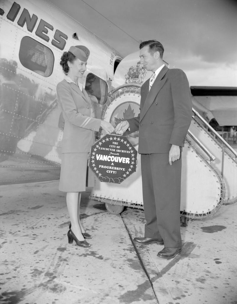 Flight attendant passing a film to a man at the airport. 1946.  Reference code: AM1184-S1-: CVA 1184-2349. Note: This photograph has been altered for promotional purposes.