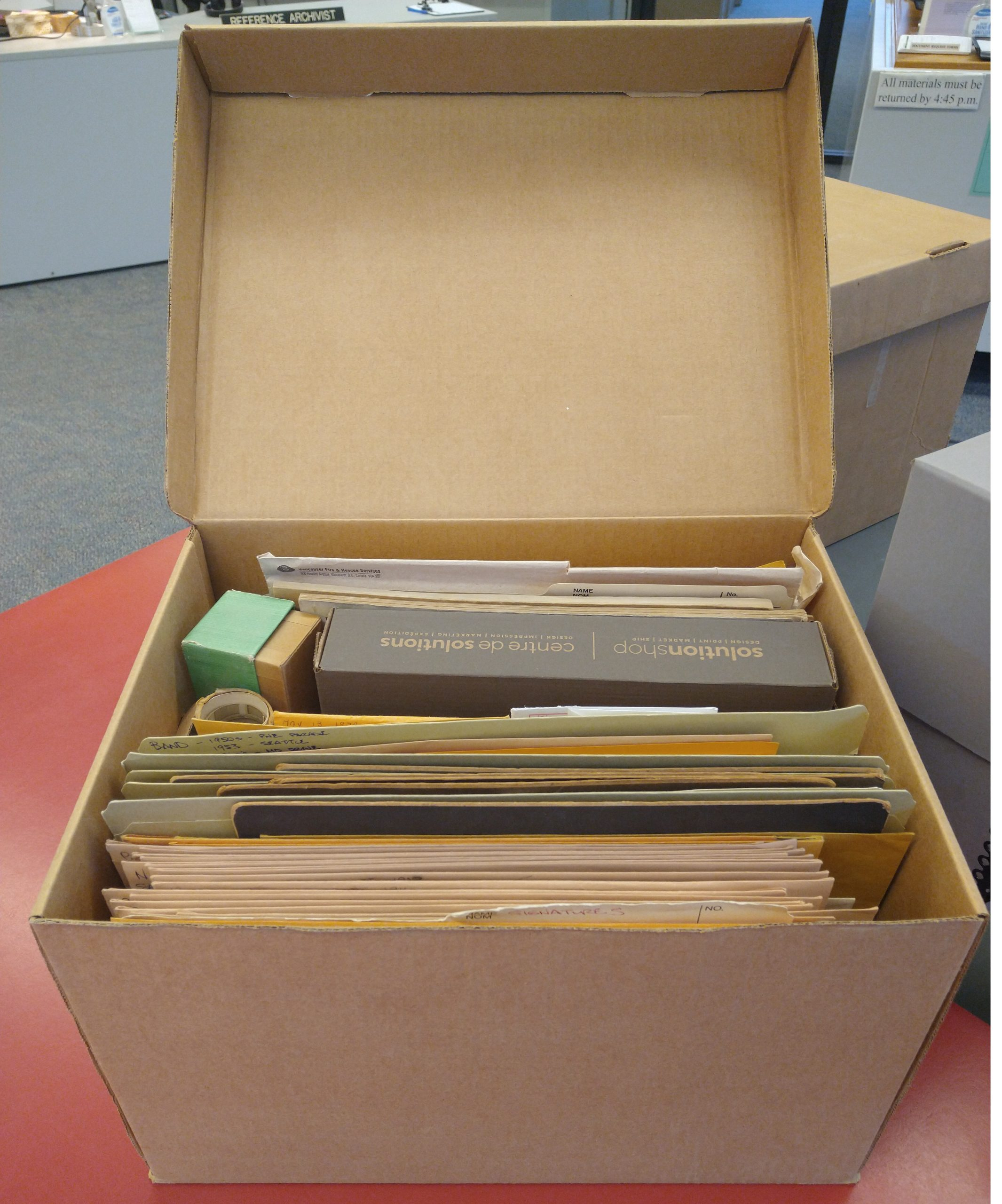 "This box containing about 100+ photographic prints is awaiting further ""TLC"" by an archivist. Photo by Kira Baker"