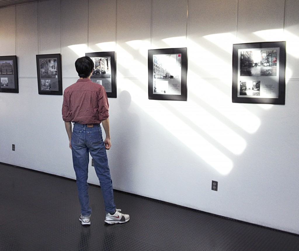 A member of the public views the Merging Time: A Modern Perspective photography exhibit. Photo credit: Christine Hagemoen.